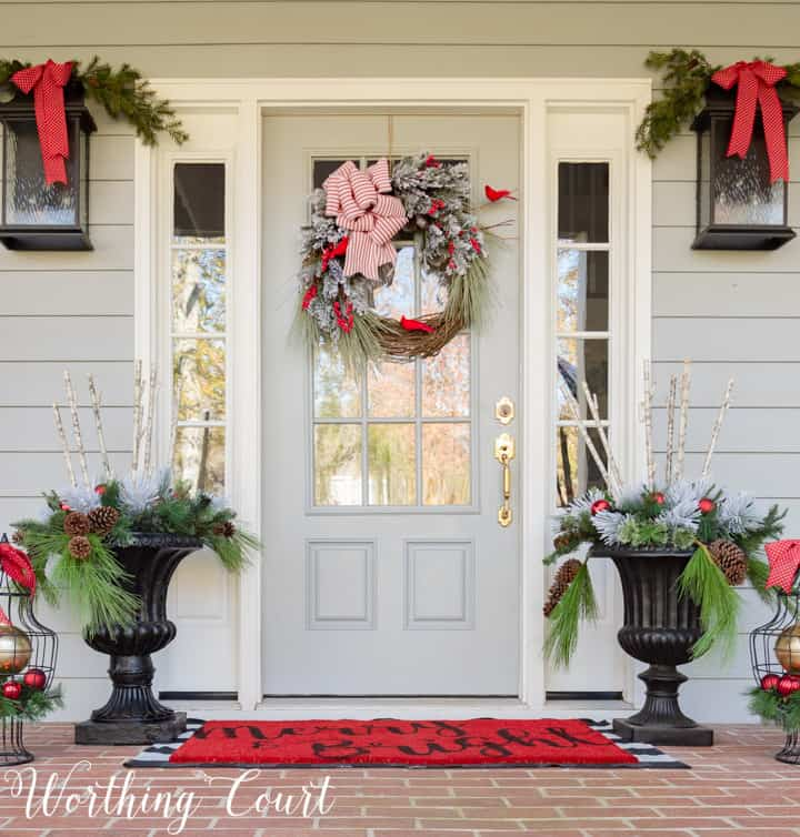 Classic red and green Christmas porch with DIY cardinal wreath #christmas #christmasporch #ourdoorchristmasdecor #diywreath #christmaswreath #farmhousechristmas #christmasurns #christmasplanters