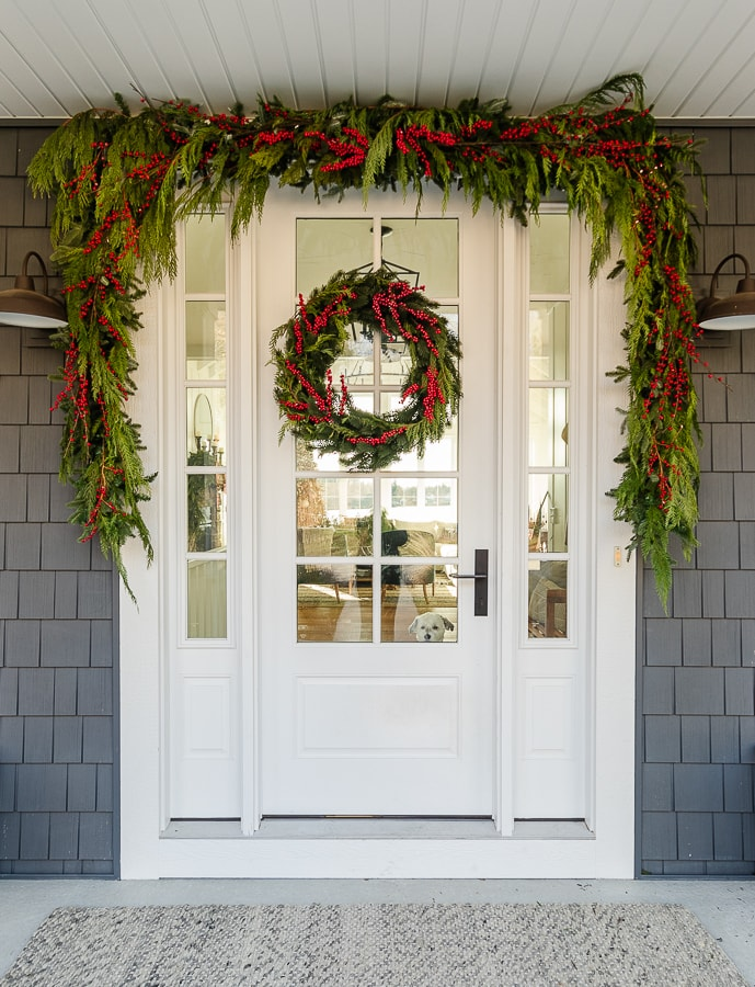 Love the red berry garland and wreath on this classic Christmas porch #christmas #christmasporch #christmasgarland #christmaswreath #diychristmas #farmhousechristmas
