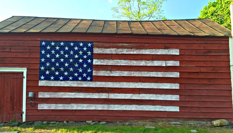 Big red barn with giant painted flag