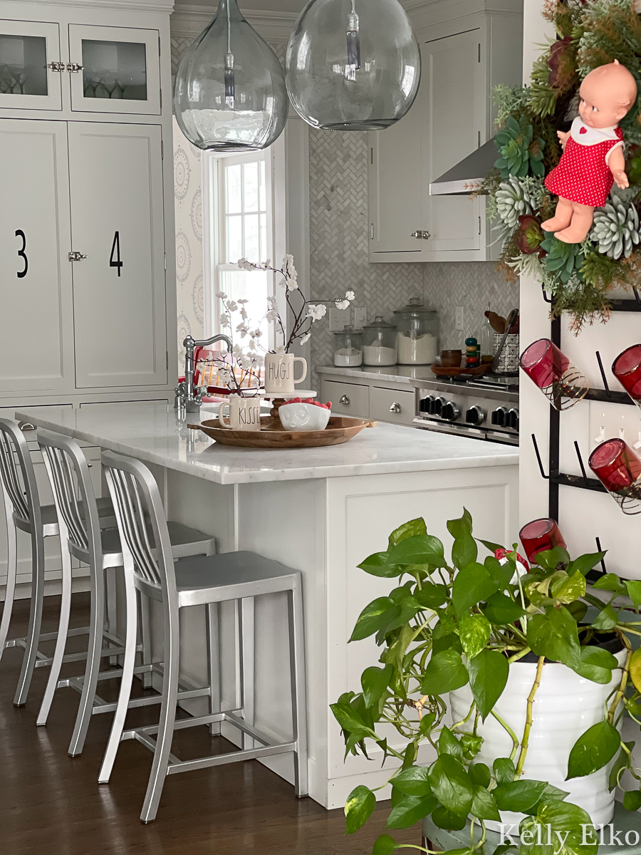 Love this white kitchen with simple Valentine decor including an adorable Kewpie doll wreath kellyelko.com