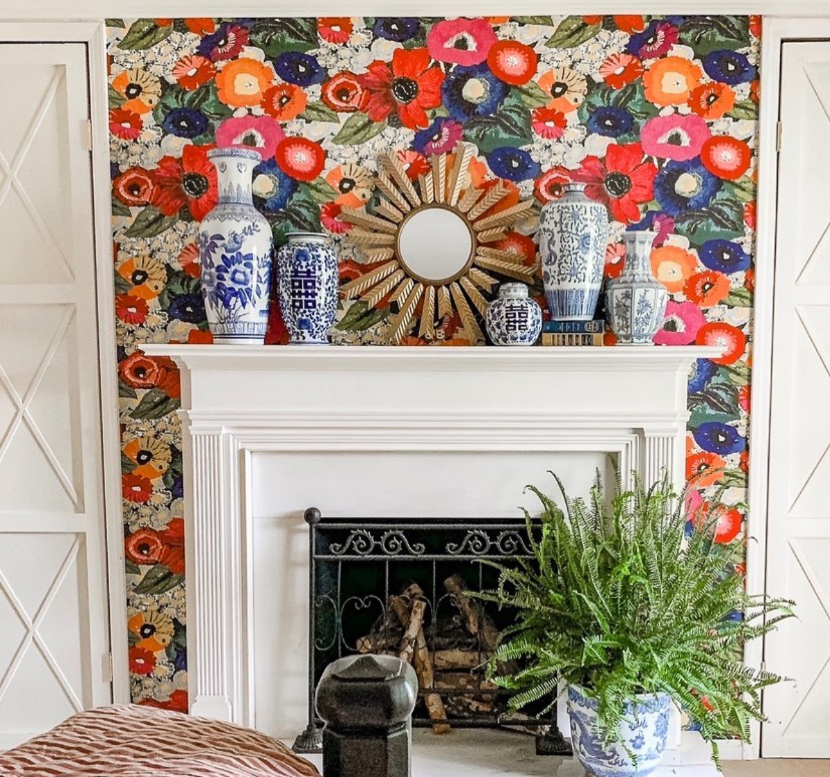 Bright and colorful floral wallpaper makes the mantel the focal point