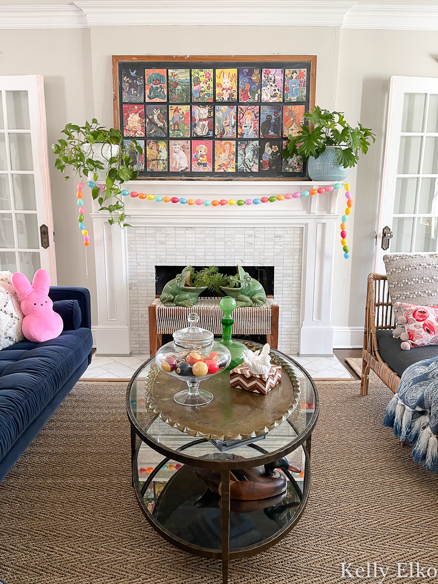 Love this spring mantel with oversized art collage, DIY egg garland and plants kellyelko.com