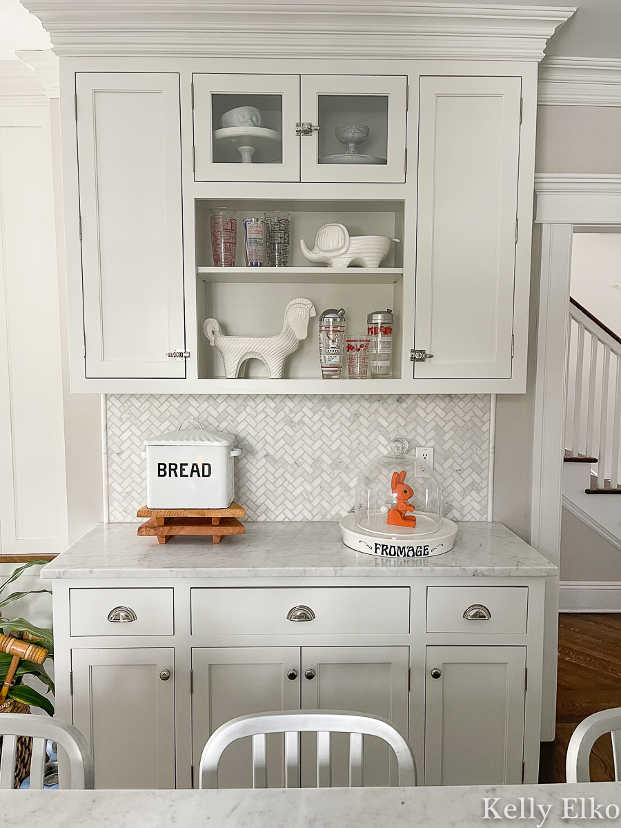 Farmhouse white kitchen with open shelves to display a vintage cocktail shaker collection kellyelko.com