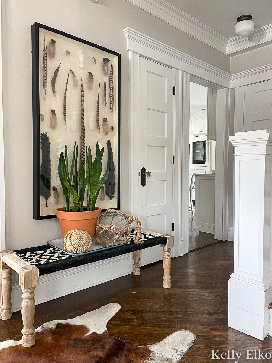 Beautiful foyer with feather art and a woven bench kellyelko.com