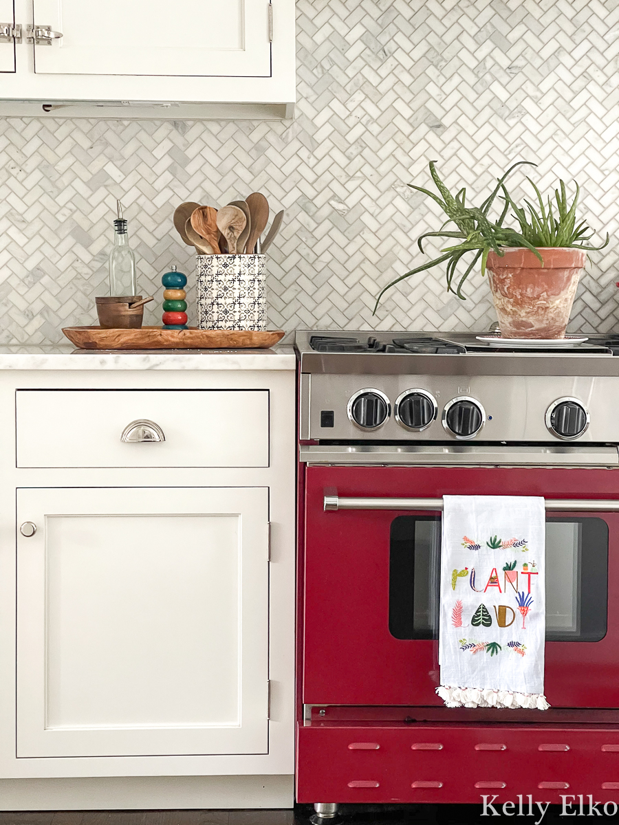Beautiful red stove in a white kitchen with herringbone marble backsplash kellyelko.com
