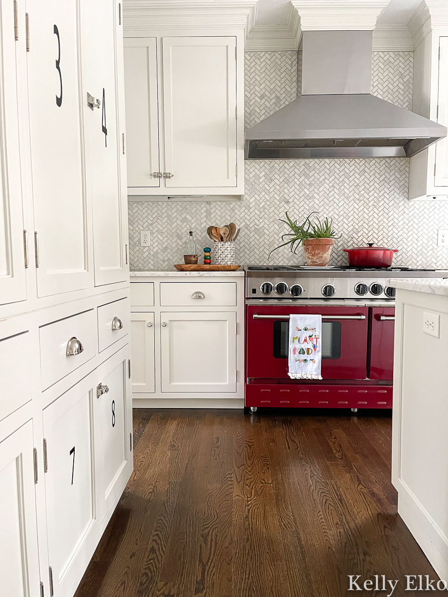 White kitchen with red stove and herringbone carrara marble backsplash kellyelko.com