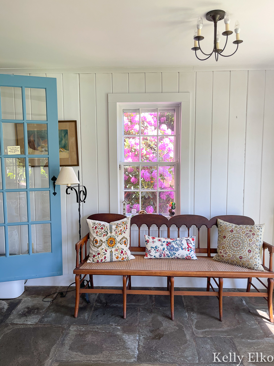Lovely sunroom with stone floor and cane bench kellyelko.com
