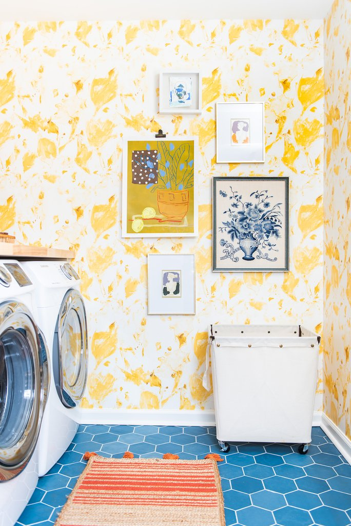 Love this stunning yellow floral wallpaper paired with vibrant blue tile floor in this fun laundry room kellyelko.com