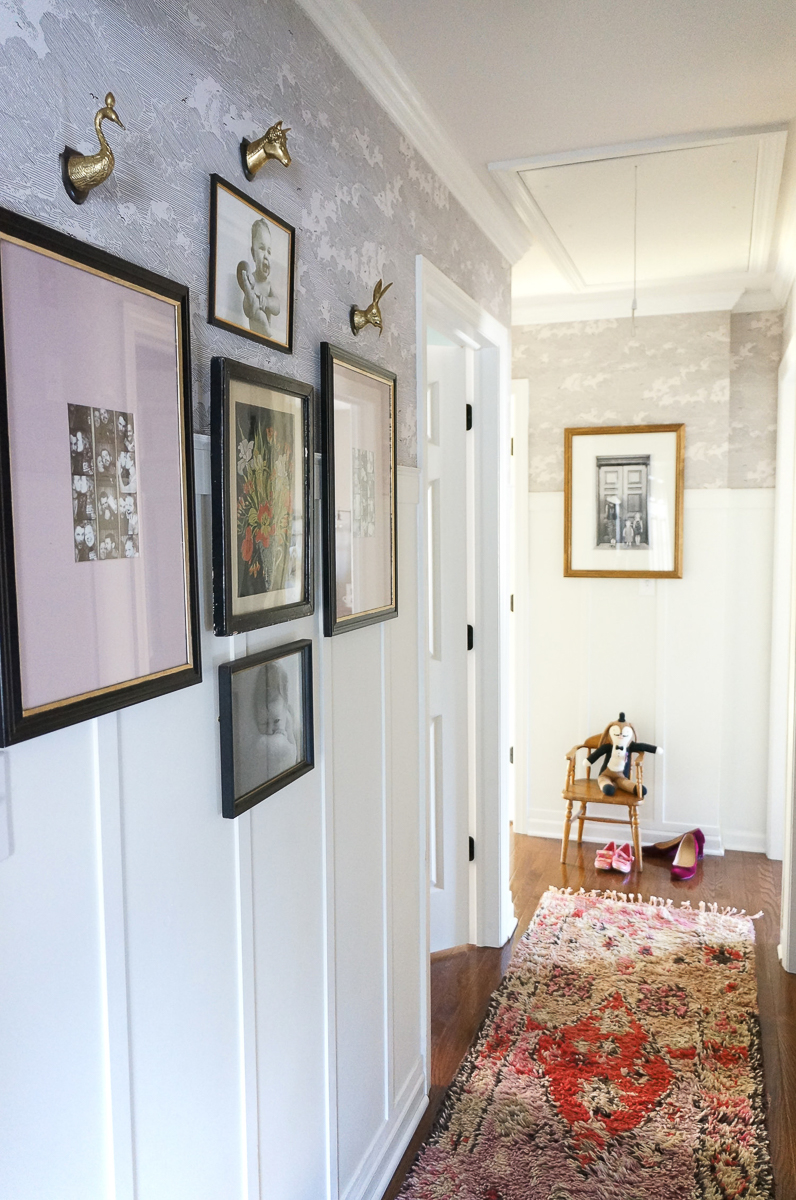 Love this hallway with planked walls, subtle gray wallpaper and gallery wall kellyelko.com