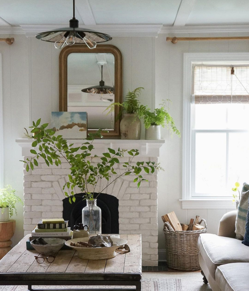 Painted brick fireplace in this stunning farmhouse filled with plants and vintage finds kellyelko.com