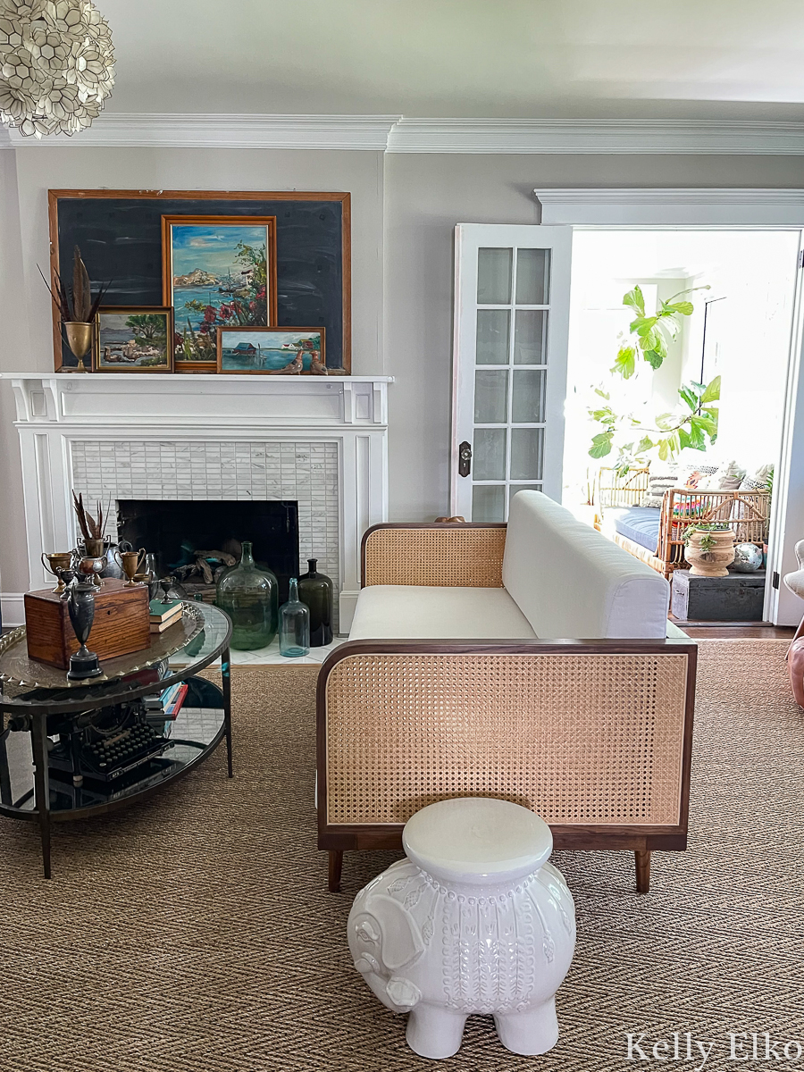 Eclectic living room tour - love the vintage art on the mantel and the cane sofa kellyelko.com
