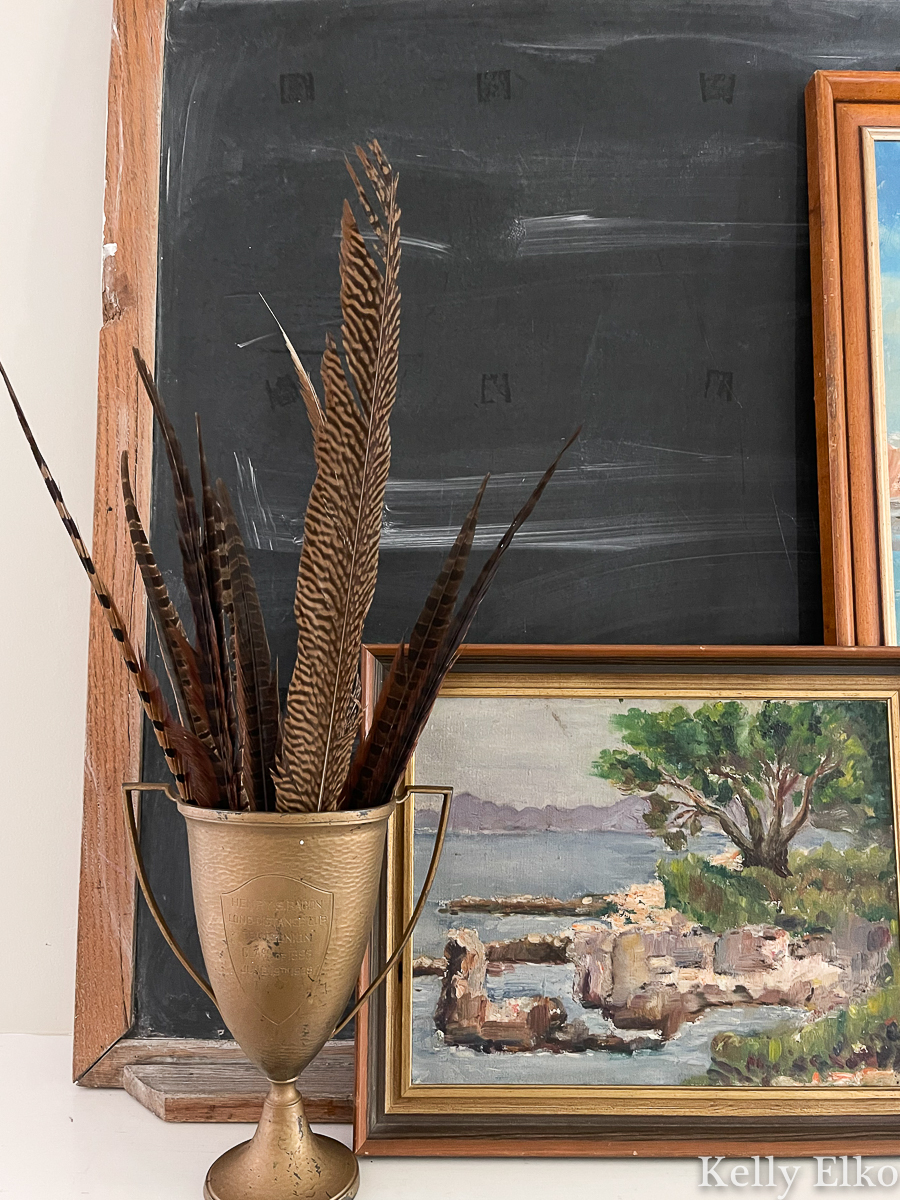 Beautiful vintage mantel with loving cup filled with feathers and vintage art kellyelko.com