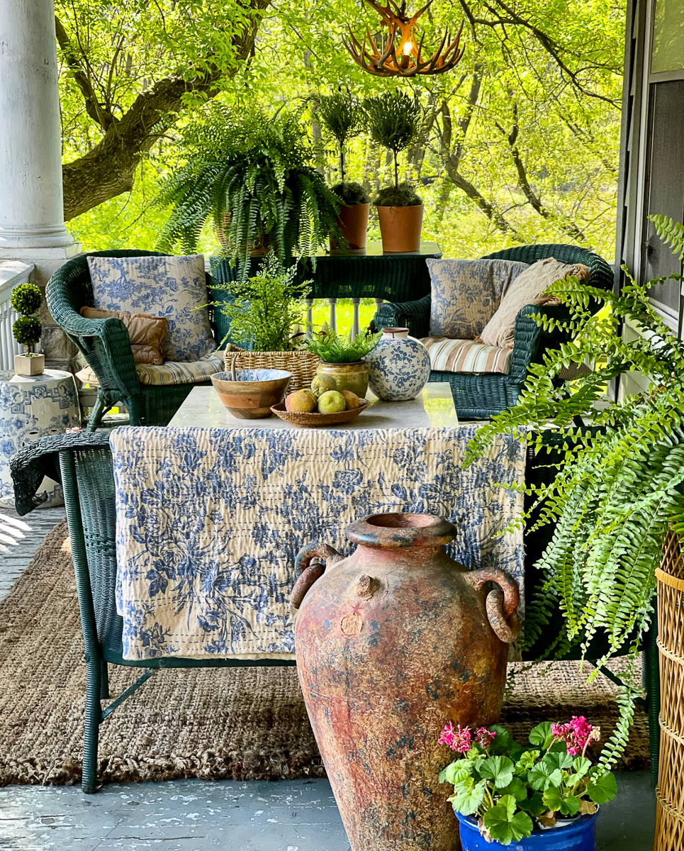 Porch goals - love the eclectic mix of wicker, plants, topiaries, quilts kellyelko.com