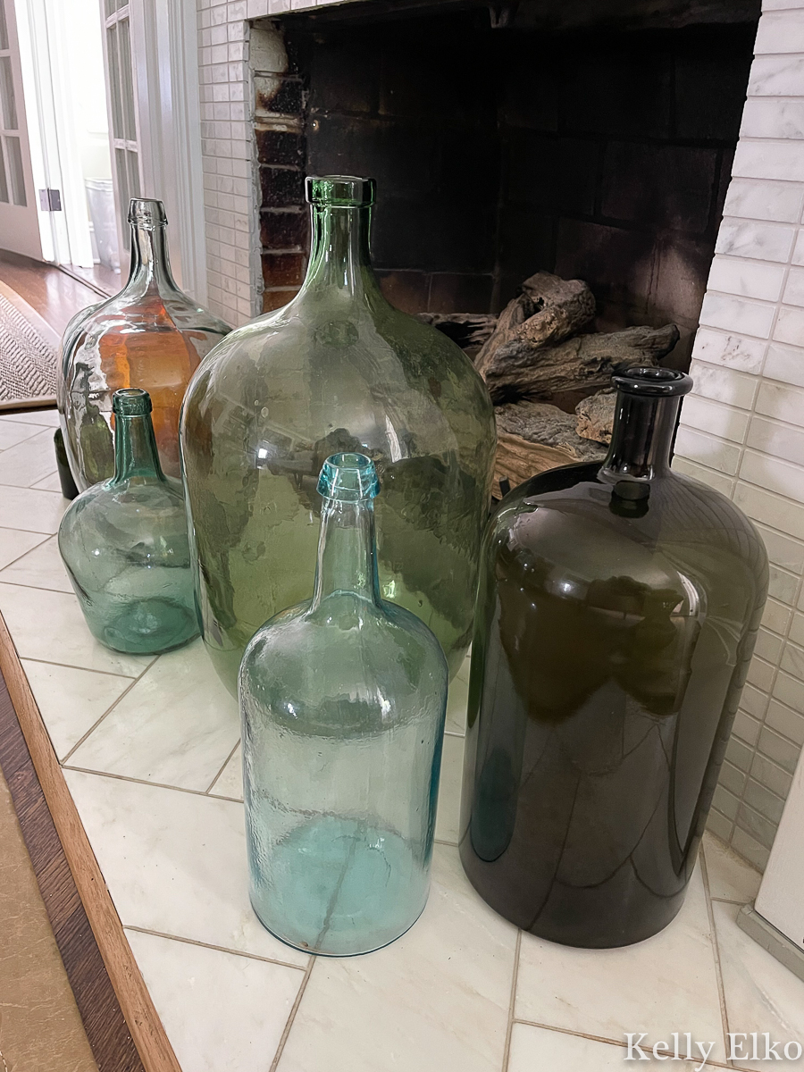Gorgeous collection of antique demijohn wine bottles on the hearth kellyelko.com