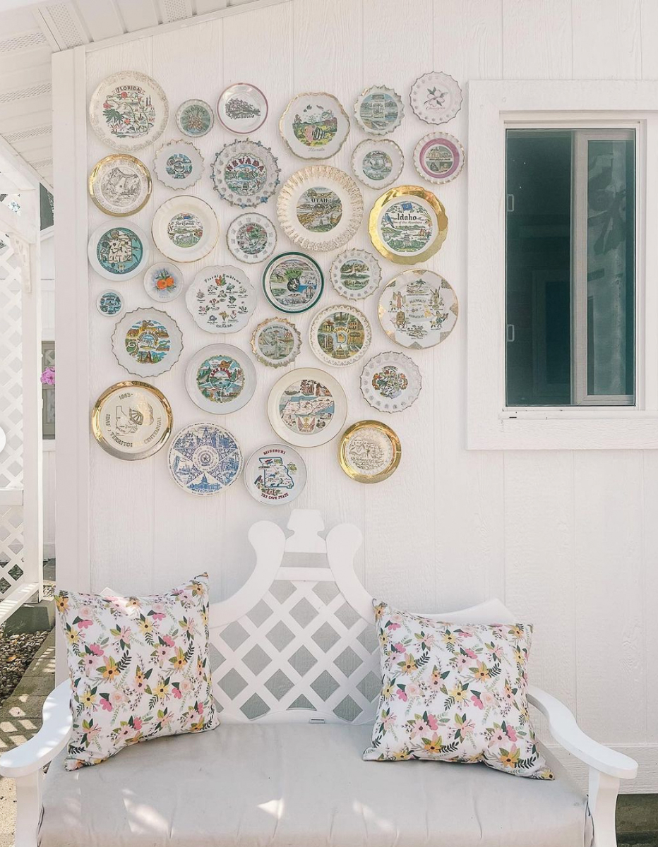 A thrifted vintage state plate wall collection hung on an outdoor wall creates a fun backdrop kellyelko.com